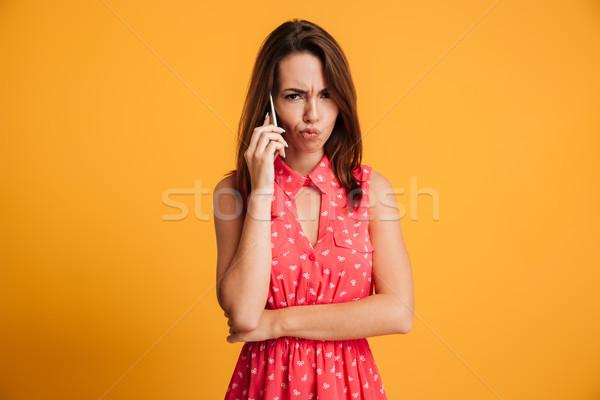 Elégedetlen barna hajú nő ruha beszél okostelefon Stock fotó © deandrobot