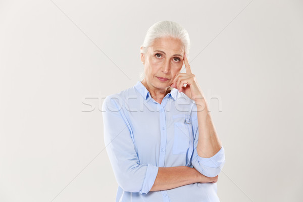 Photo of thinking old lady in blue shirt, looking at camera Stock photo © deandrobot
