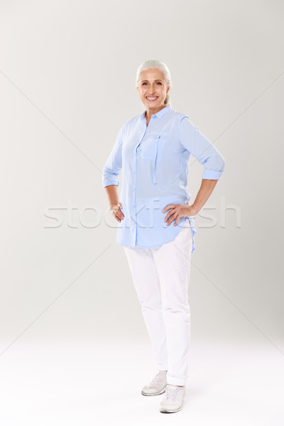Full-length portrait of cheerful mature woman in blue shirt and  Stock photo © deandrobot