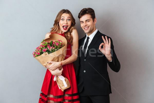 Portrait of a young happy couple holding flower bouquet Stock photo © deandrobot