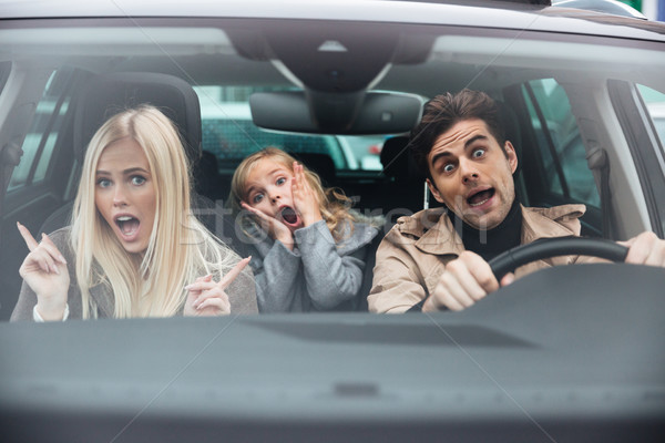 Shocked man sitting in car with his wife and daughter Stock photo © deandrobot