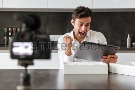 Happy young man filming his video blog episode Stock photo © deandrobot