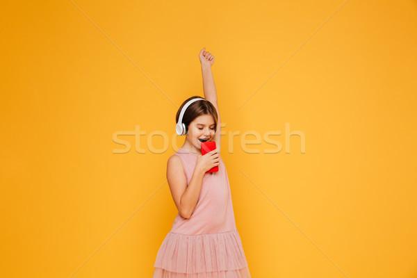 Mały pani słuchawki śpiewu smartphone odizolowany Zdjęcia stock © deandrobot