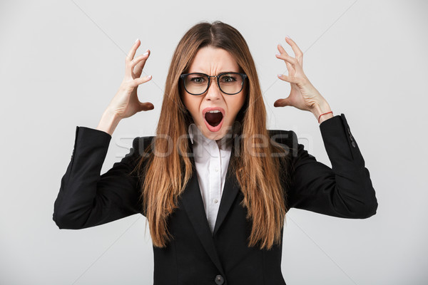 Angry lady screaming and holding hands near head isolated Stock photo © deandrobot