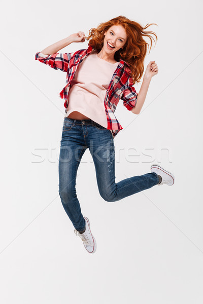 Happy young redhead lady jumping isolated Stock photo © deandrobot