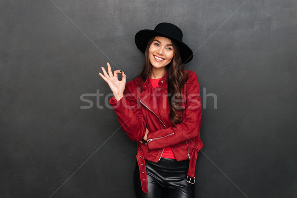 Happy young woman wearing hat showing okay gesture. Stock photo © deandrobot