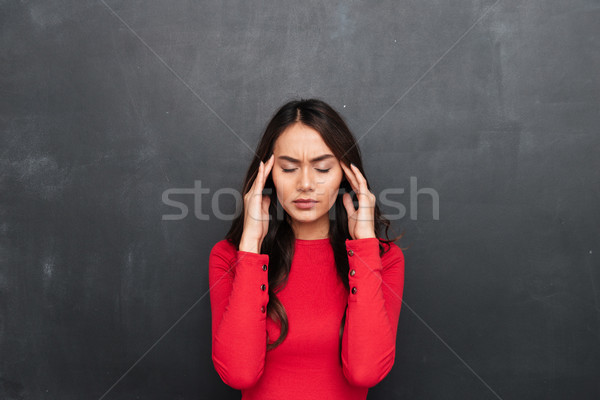 Confused brunette woman in red blouse having headache Stock photo © deandrobot
