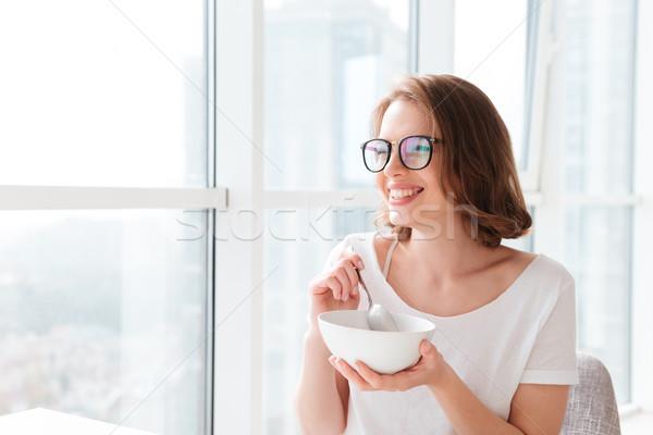 Derűs fiatal csinos nő eszik gabonapehely kép Stock fotó © deandrobot