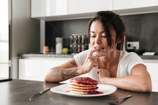 Głodny młoda kobieta posiedzenia kuchnia domu zdjęcie Zdjęcia stock © deandrobot