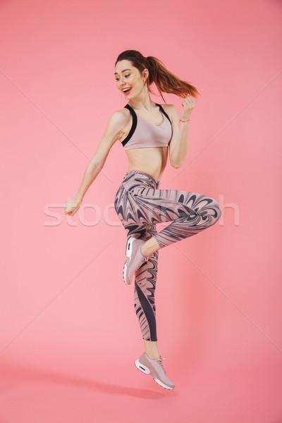 Full length image of Happy sportswoman doing fitness exercise sideways Stock photo © deandrobot