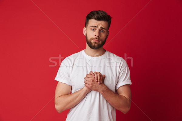 Hopeful young man make please gesture. Stock photo © deandrobot