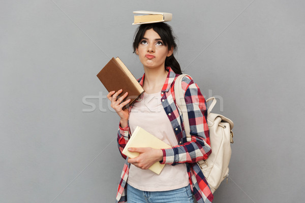 Sad displeased young lady holding book. Stock photo © deandrobot