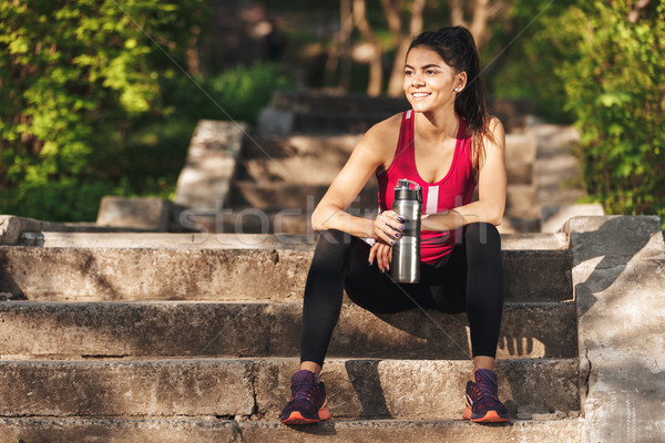 Picture of Smiling sports woman relaxing on stairs after training Stock photo © deandrobot