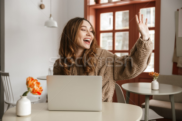 Photo of joyous young woman in sweater looking aside with broad  Stock photo © deandrobot