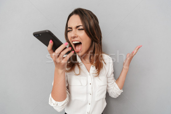 Portrait of a furious young business woman yelling Stock photo © deandrobot