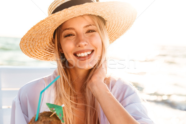 Photo of happy young woman 20s in summer straw hat laughing, and Stock photo © deandrobot