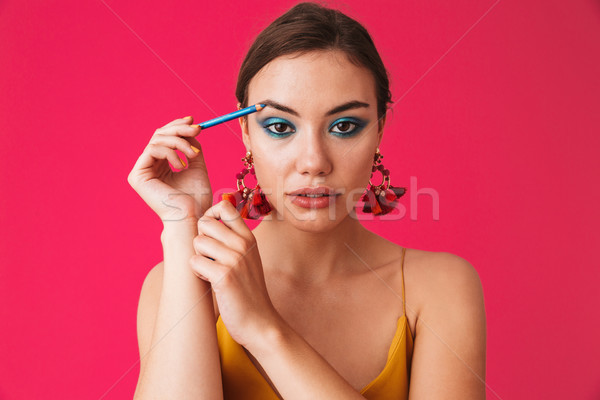 Image of caucasian stylish woman 20s wearing earrings smiling an Stock photo © deandrobot