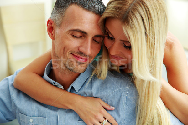 Couple hugging with eyes closed at home Stock photo © deandrobot