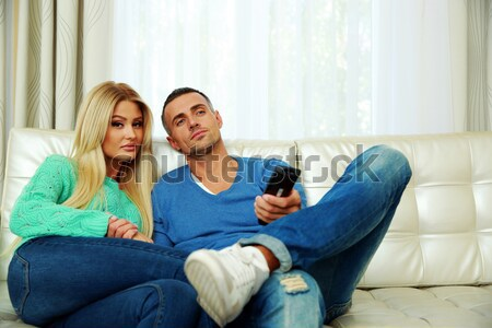 Beautiful couple bickering to change tv channel on remote control Stock photo © deandrobot