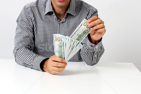 Midsection of businessman holding banknotes at desk Stock photo © deandrobot