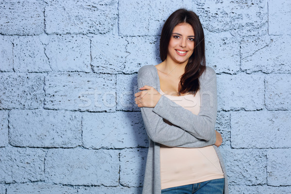 Young beautiful happy woman in casual cloths against brick wall Stock photo © deandrobot