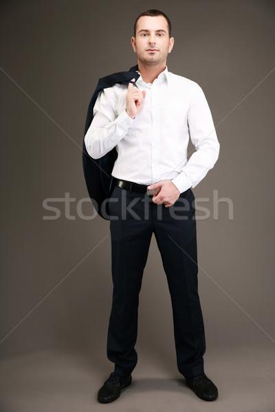 Full length portrait of a businessman holding his jacket over shoulder Stock photo © deandrobot