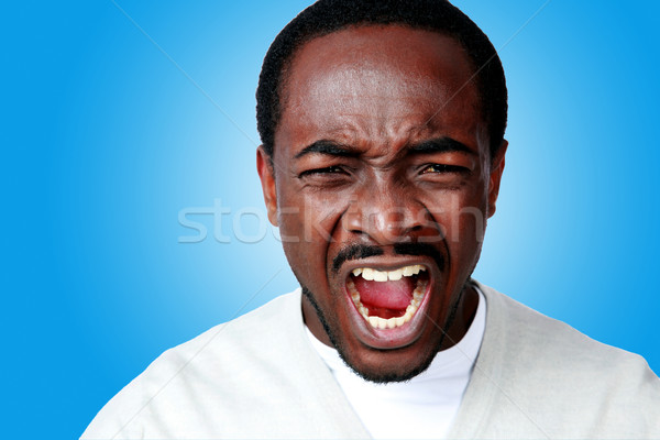 Angry african man screaming on blue background Stock photo © deandrobot