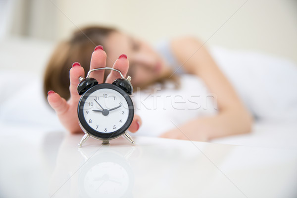 Sleepy woman in bed extending hand to alarm clock. Focus on clock Stock photo © deandrobot