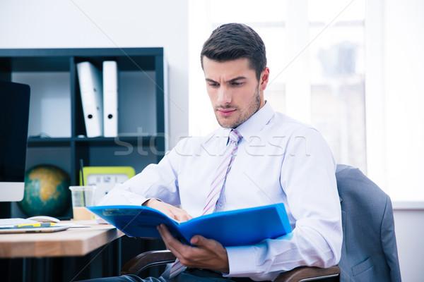 Empresario sesión mesa lectura documento oficina Foto stock © deandrobot
