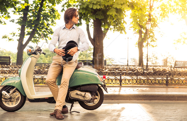 Stylish man standing near his scooter with helmet in his hands and looking away. sunflare. Stock photo © deandrobot