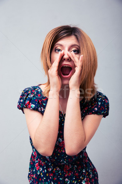 Woman shouting with palms Stock photo © deandrobot