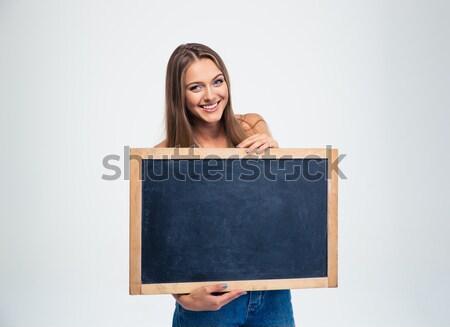 Smiling female student holding blank board  Stock photo © deandrobot