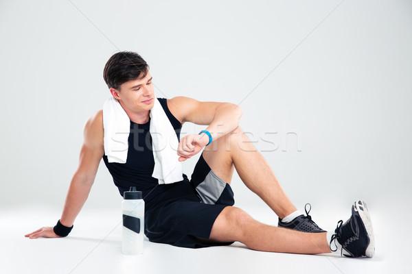 Man looking on fitness tracker Stock photo © deandrobot