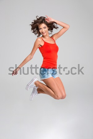 Happy smiling inspired girl in jump Stock photo © deandrobot
