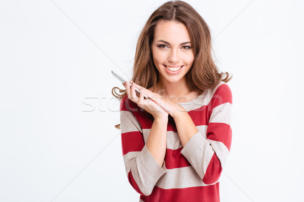 Smiling woman covering microphone on smartphone with palm Stock photo © deandrobot