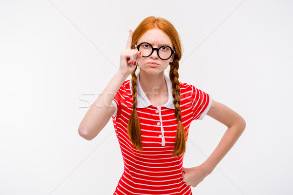 Strict young woman with two braids pointing up  Stock photo © deandrobot