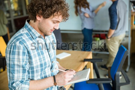 Concentrated male writing in notebook and workinng with partners Stock photo © deandrobot