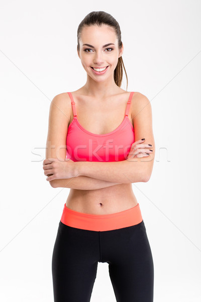 Beautiful smiling young sportswoman standing with crossed arms Stock photo © deandrobot