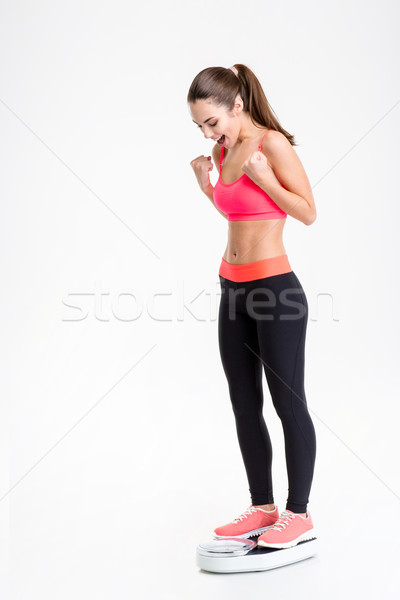 Happy excited young sportswoman standing on weigh scale  Stock photo © deandrobot