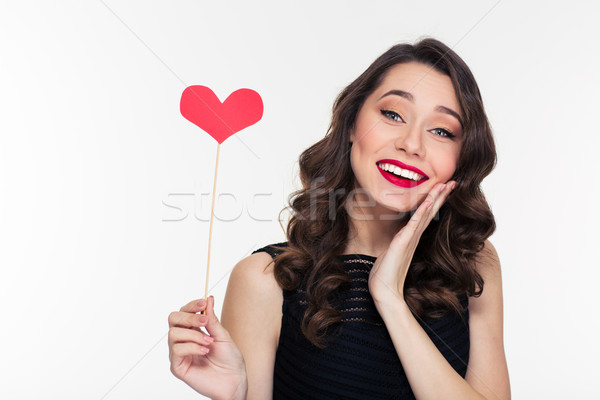 Stock photo: Happy pretty shy female with retro hairstyle holding heart props