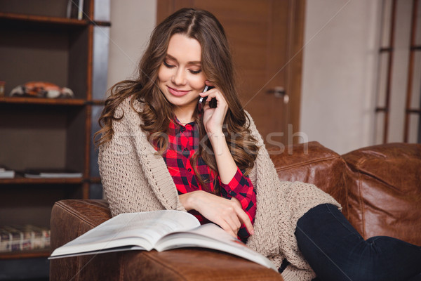 Woman talking on the phone and reading magazine Stock photo © deandrobot