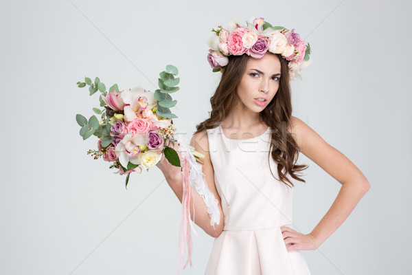 Attractive irritated woman in rose wreath showing bouquet of flowers  Stock photo © deandrobot