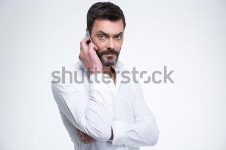 érett üzletember beszél telefon néz kamera Stock fotó © deandrobot