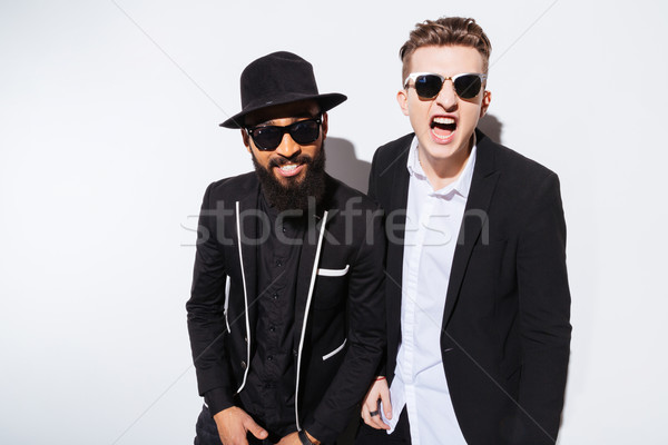 Two irritated modern young men shouting and looking at camera Stock photo © deandrobot