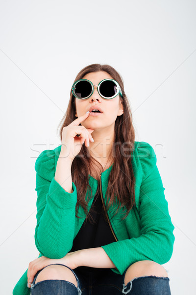 Amazed woman in round sunglasses sitting and looking up Stock photo © deandrobot