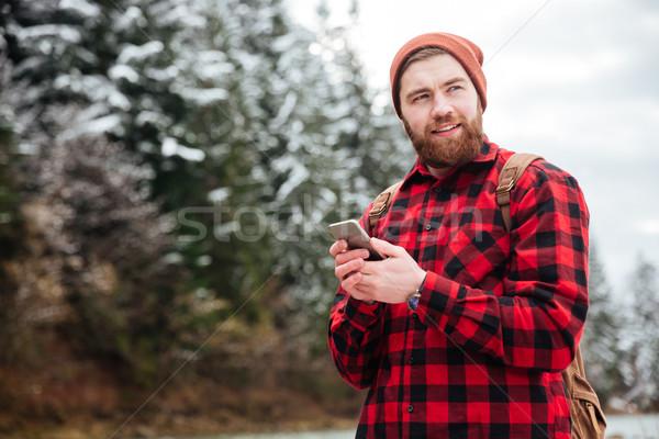 Boldog férfi természetjáró okostelefon másfelé néz telefon Stock fotó © deandrobot