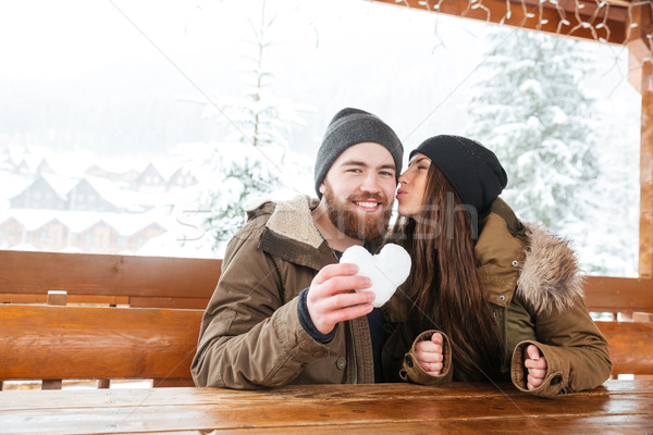 Couple kissing and holding heart made of snow in winter Stock photo © deandrobot