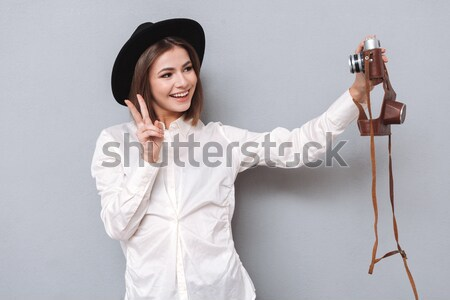 Attractive young woman in bathrobe standing and holding hair dryer Stock photo © deandrobot