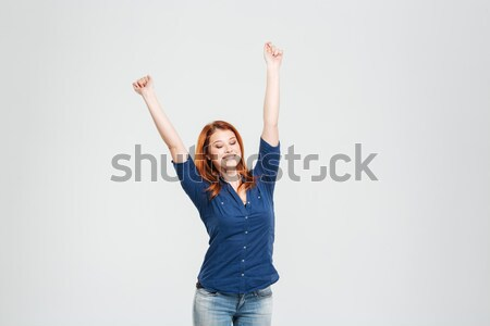 Happy relaxed woman stretching with eyes closed and raised hands  Stock photo © deandrobot