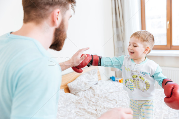 Father playing with his son in boxing gloves at home  Stock photo © deandrobot
